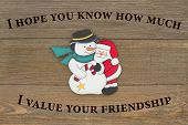 Old Fashion Christmas Friendship Message, A Retro Snowman And Santa Claus Hugging On Weathered Wood  poster