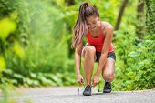 Happy woman tying running shoes getting ready to walk or run jogging in outdoor forest. Asian fit gi poster