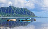 A Perfectly Still Kaneohe Bay Creates A Perfect Reflection On The Mountains And Old Boats poster