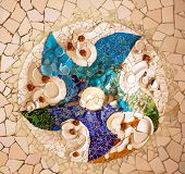 stock photo of gaudi barcelona  - Antoni Gaudi ceramic mosaic design in Guell Park Barcelona Catalonia Spain. Guell Park is a residential complex designed by Antnoi Gaudi between 1900-1914 which is now a public park. Now a UNESCO World Heritage Site. Design created by plates.