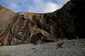 picture of shale  - A pebble shore leads to a rock fall under a shale cliff with a blue sky and cloud in the distance - JPG