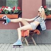 picture of roller-derby  - Young blonde woman in roller skates having fun - JPG