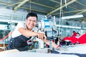 stock photo of chain  - Indonesian worker using a cutter  - JPG