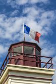 stock photo of acadian  - An Acadian flag on top of a lighthouse in rural Prince Edward Island - JPG