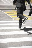 stock photo of zebra crossing  - Unrecognizable businessman rollerblading and crossing zebra - JPG