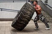 pic of strongman  - Muscular Man with Truck Tire doing crossfit style workout turning tire over - JPG
