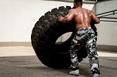 image of strongman  - Muscular Man with Truck Tire doing crossfit style workout turning tire over - JPG