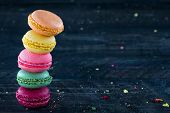 picture of french pastry  - Two piles of colorful macaroons on a dark black wooden background with selective focus and small crumbs on the table - JPG