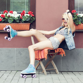stock photo of roller-derby  - Young blonde woman in roller skates having fun - JPG