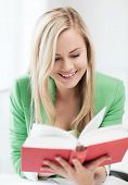 education concept - picture of smiling young woman reading book at school