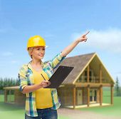 repair, construction and maintenance concept - smiling woman in helmet with clipboard pointing finge