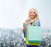 retail and sale concept - smiling woman with many shopping bags
