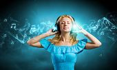 Young lady in blue dress with headphones enjoying the music