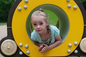 Young girl sitting in crawl tube