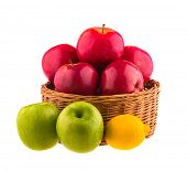 Red and green apples, and lemon in a wooden basket, isolated on white background.