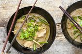 picture of curry chicken  - Bowls of tasty Thai green curry served with chopsticks made from nutritional bean sprouts broccoli chicken coconut milk corianderand green beans view from above - JPG