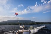 stock photo of chute  - Paragliding from skiboat towing chute and rider over waters - JPG