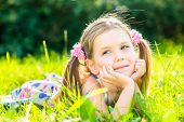 picture of ponytail  - Cute smiling little girl with two blond ponytails laying on grass in summer park outdoor portrait - JPG
