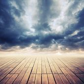 picture of cloudy  - Wooden floor with perspective and stormy cloudy sky toned effect - JPG