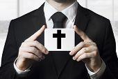 pic of funeral  - undertaker man in black suit holding sign black cross funeral - JPG