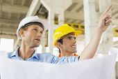 pic of headgear  - Male architect explaining building plan to colleague at construction site - JPG