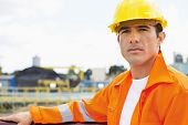 stock photo of headgear  - Portrait of handsome mid adult man wearing protective workwear at construction site - JPG
