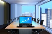 stock photo of computer-screen  - meeting room in front focus placed on graph shiwing progress on laptop screen - JPG