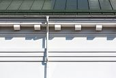 stock photo of downspouts  - House roof gutters and downspout on the wall - JPG
