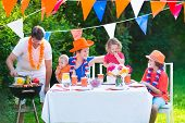 foto of holland flag  - Happy big Dutch family with kids celebrating a national holiday or sport victory having fun at a grill party in a garden decorated with flags of Netherlands screaming Hup Holland - JPG