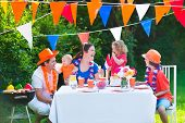 image of holland flag  - Happy big Dutch family with kids celebrating a national holiday or sport victory having fun at a grill party in a garden decorated with flags of Netherlands screaming Hup Holland - JPG