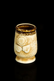 foto of loamy  - Clay cup handmade with ornaments in the shape of a flower isolated on a black background  - JPG