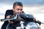 image of stubborn  - young man with a stubborn look leaned on the steering wheel of his bike - JPG