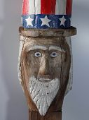 pic of uncle  - A painted folk art figure of Uncle Sam is carved out of a chunk of wood.