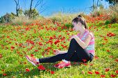 stock photo of windflowers  - Teenage girl with braces on her teeth in a field of wild red anemone coronaria  - JPG