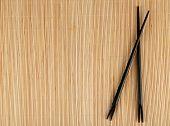 foto of bamboo  - Pair of chopsticks on light bamboo mat background - JPG