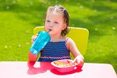 stock photo of eat grass  - Toddler kid girl drinking eating macaroni pasta in garden turf grass outdoor - JPG