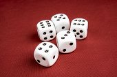 pic of dice  - Macro of five dice on cloth red surface with shallow depth of field focusing on the front dice - JPG