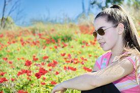 pic of windflowers  - Teenage girl with braces on her teeth in a field of wild red anemone coronaria  - JPG