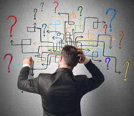picture of confusing  - Businessman trying to solve a maze questions - JPG