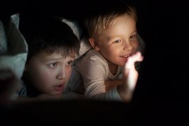 picture of boys night out  - Two boys lying on bed under blanket at night. They