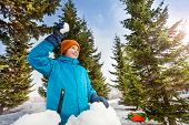 image of snowball-fight  - Happy boy ready to throw snowball while standing behind the snow wall with fir forest on the background during beautiful winter day - JPG
