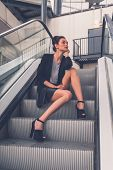 stock photo of mini-skirt  - Gorgeous young brunette in black skirt posing on an escalator - JPG
