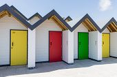 foto of beach-house  - Colourful doors of yellow green and red with each one being numbered individually of white beach houses on a sunny day in Swanage - JPG