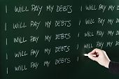 foto of punishment  - I will pay my debts sentence written repeatedly on blackboard as a punishment - JPG