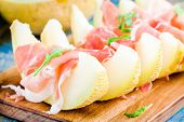 foto of melon  - fresh melon with thin slices of prosciutto and arugula leaves - JPG