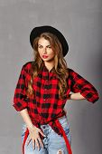 picture of young woman posing the camera  - Young sexy woman in a hat plaid shirt and jeans posing in studio look at the camera - JPG
