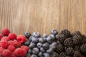 picture of blackberries  - raspberries and blackberry scattered on the wooden table - JPG