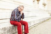 stock photo of memory stick  - Portrait of pensive mature man in glasses and plaid shirt resting leaning on his wooden walking stick - JPG