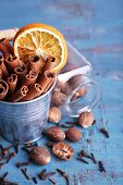 image of cinnamon sticks  - Cinnamon sticks with dried orange in metal bucket - JPG
