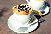 foto of treble clef  - Cups of cappuccino with treble clef on foam on table in cafe - JPG